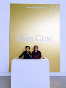 Wibke Ladwig und Jutta Frings vor dem schönen goldenen Plakat in der Eingangshalle der Bundeskunsthalle